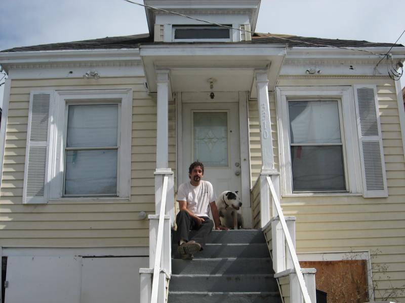 Omar El-Baroudi on the front steps of his West Oakland home with his dog Ling-Ling.