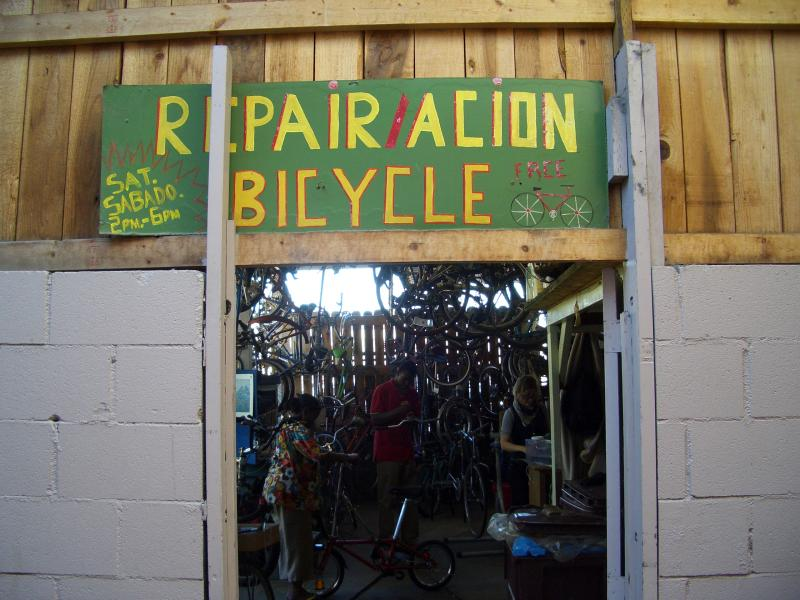 Entrance to the shop, with volunteer-painted sign. Inside: Kathleen Mills, Steven Hobdy and Morgan Kanninen