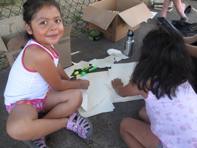 Two neighborhood kids enjoy art time while their parents discuss future plans for the library.