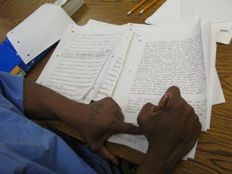 inmate writing draft of appeal inside law library