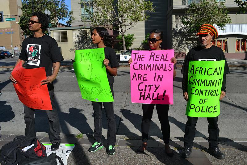 Demonstrators hold signs at a vigil for Alan Blueford last May at Oakland's police headquarters.
