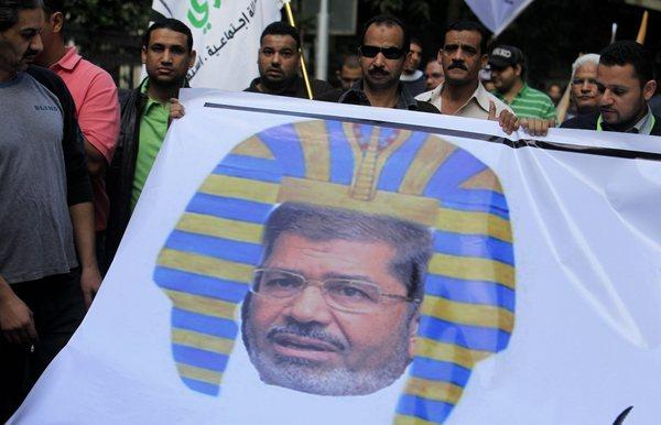 Egyptian protesters hold a banner depicting Egyptian President Morsi…