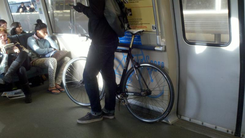 A bike commuter rides BART during a pilot period that allows bikes on trains during peak hours.