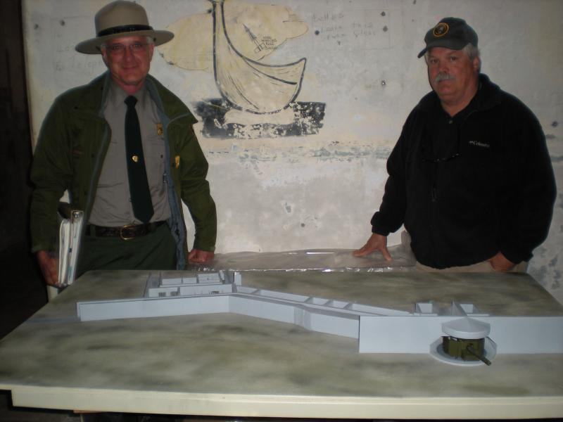 Park historian Steve Haller and retired park ranger John Martini examine a model of Battery Townsley.