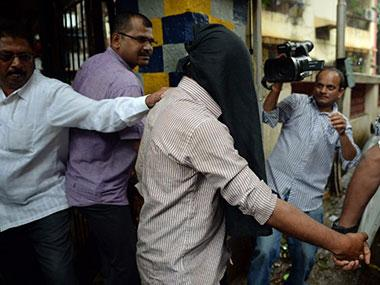 Police officials escort a suspect in the gang-rape of a female photographer, from a crime branch unit station in Mumbai.
