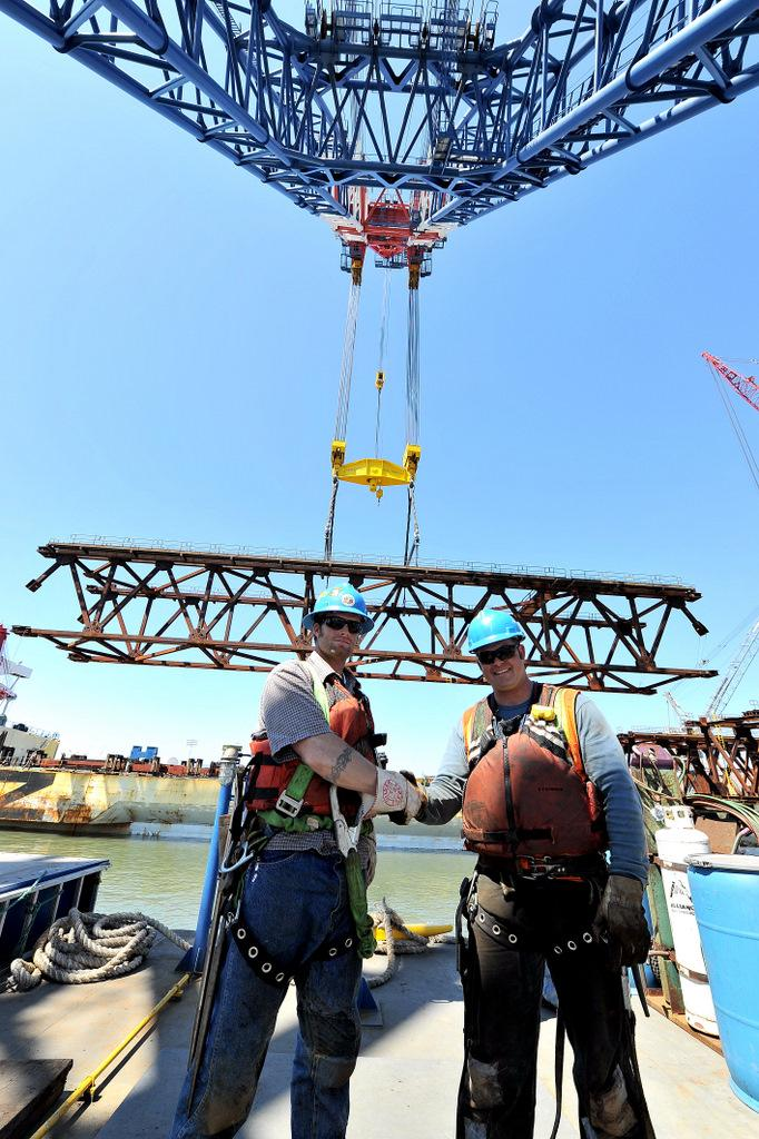 Two ironworkers on a barge, under a huge crane (via Jerry Kubala Jr.)