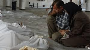 In this citizen journalism image provided by the Local Committee of Arbeen, a man and woman mourn over the dead bodies of Syrian men after an alleged poisonous gas attack