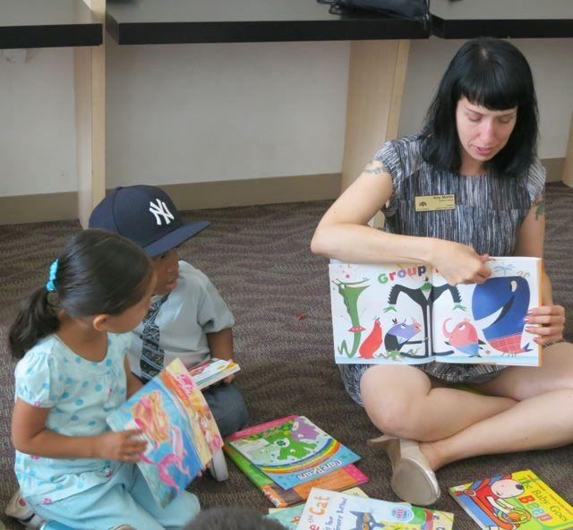Oakland Public Library children's librarian reads at the Eastmont Social Service Agency.