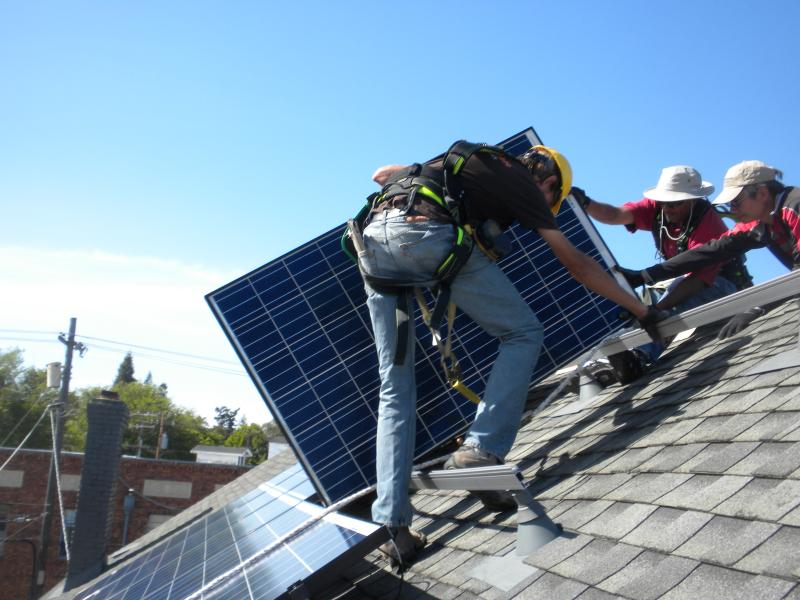 Solar workers installing panels on the Shawl Anderson Dance Center