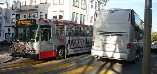 "A Muni bus passes a ""Google Bus"" in San Franisco (photo by Sven Eberlein)"