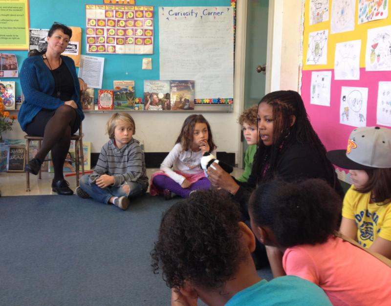 Jessy Jones and her third graders looks on as Principal Tracy Peoples shares in the community circle