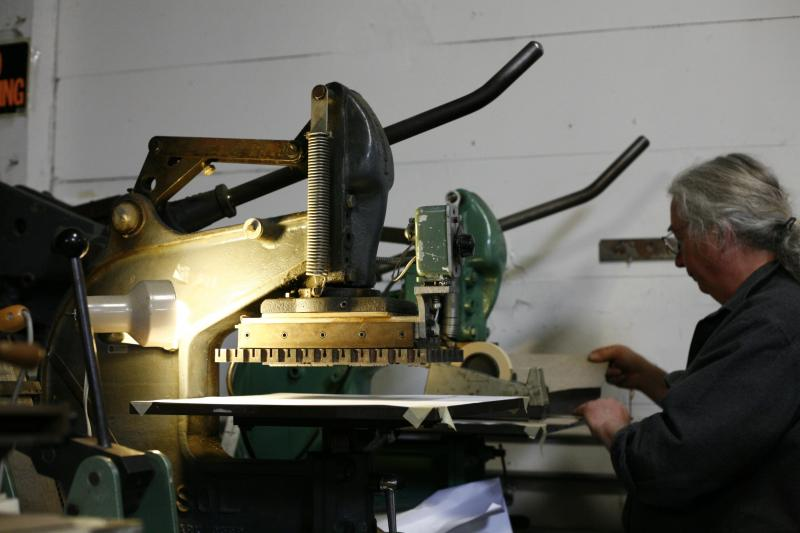 Tim James working at the gold stamping press