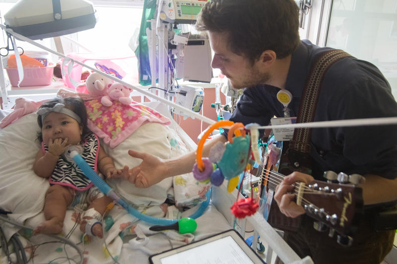 Oliver Jacobson is a music therapist at UCSF Benioff Children's Hospital. Here, he plays a session with one of his patients, Maia Mead.