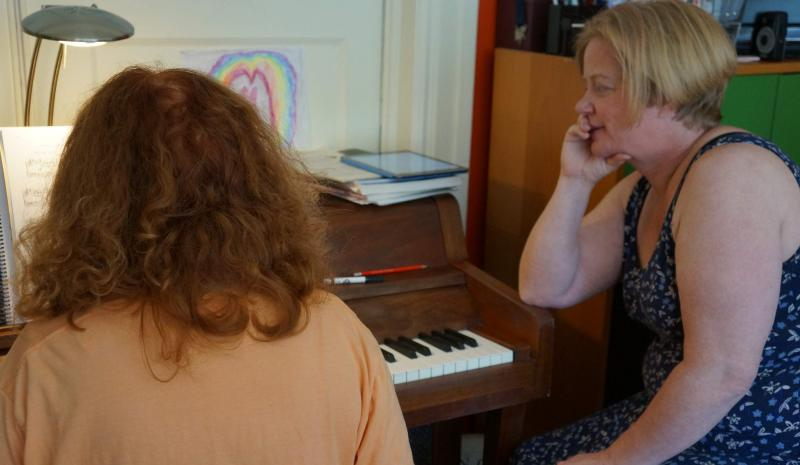Sandy Mix teaches piano to Diane Wilson.
