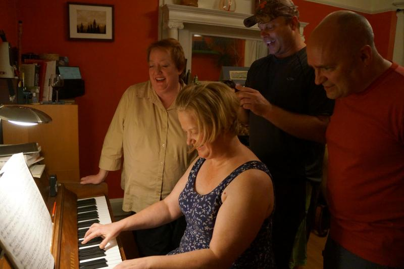 Sandy Mix plays piano as friends Carolyn Oliss, Bjorn Holtan, and Tim Bland sing.