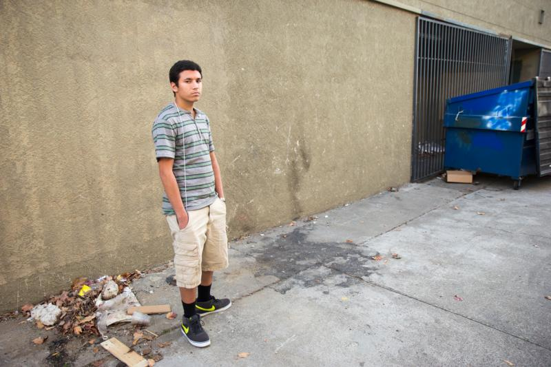 Ricky Brum standing in an alley in Manteca, California near the scorch mark left behind by a fire he set to cardboard boxes.