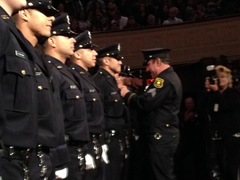 Officer Nicholas Ramos gets his new badge from his father.