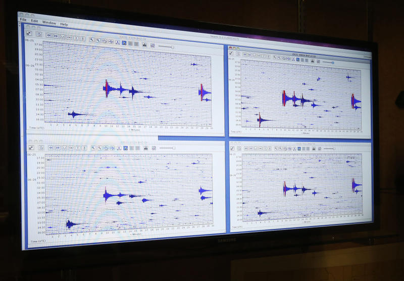 A computer screen displays real-time monitoring of seismic activity