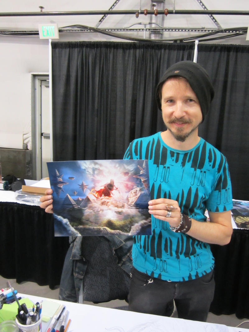 """Artist Jason Felix with poster of his most popular card """"All Is Dust."""""""
