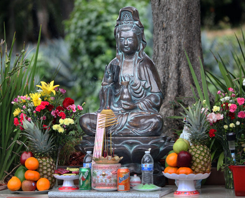 A statue of Kwan Yin, the Buddhist goddess of compassion, at a streetcorner shrine in Oakland.