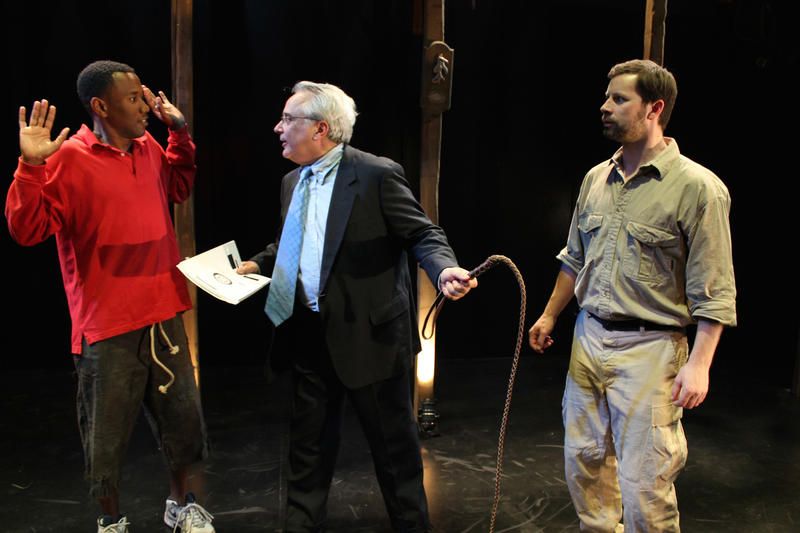Donald Rumsfeld (c, David Sinaiko) defends his involvement in the torture reports to Frederick Douglass (l, Giovanni Adams) after rescuing him from Edward Covey (r, Geoffrey Nolan) in Cutting Ball Theater's Mount Misery.