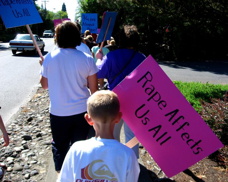 A boy marching with his mom at the Walk a Mile in Her Shoes men's march to raise awareness about rape, sexual assault, and gender violence, September 8th, 2007, in Beaverton, OR.