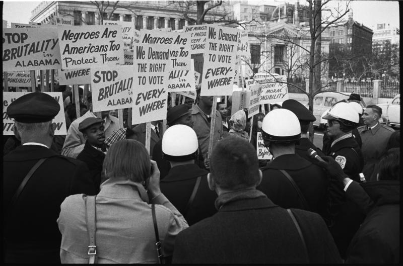 "African American demonstrators outside the White House March 12, 1965 with signs reading, ""We demand the right to vote, everywhere"" and protesting police brutality against civil rights demonstrators in Selma, Alabama"