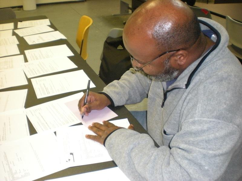 A Reentry client writing down job leads at job club