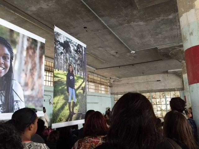 Visitors view photomurals in The Sentence Unseen: Portraits of Resilience