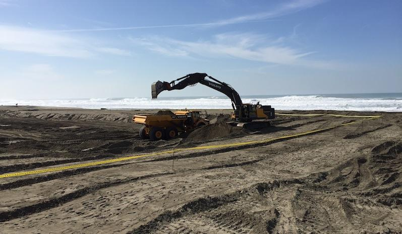 An excavator fills a dump truck with sand at the north end of Ocean Beach.