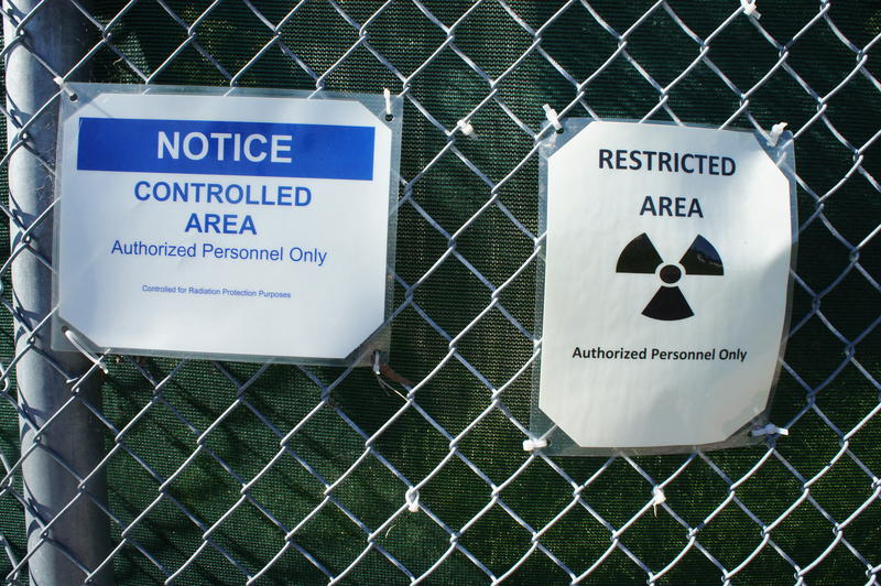 Signs on a fence warn passersby to keep out