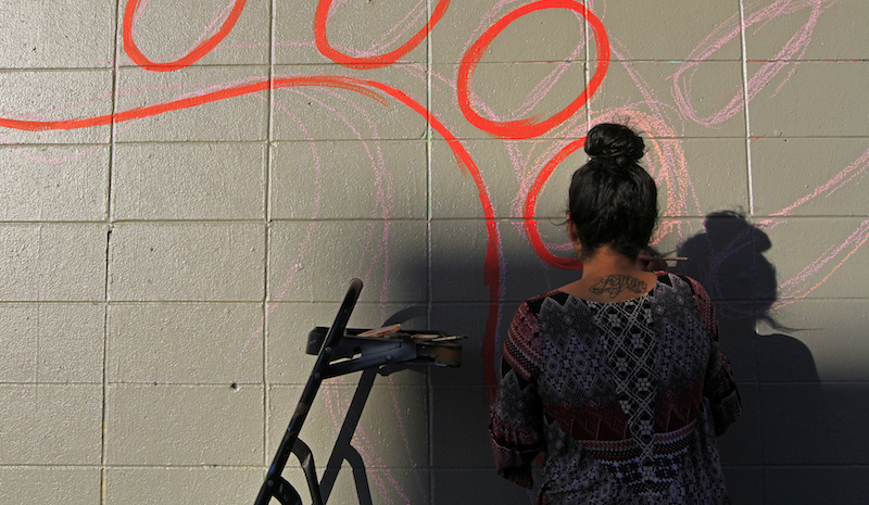 Allison Santiago, program coordinator, start the outlines of a mural honoring Native American poet and activist John Trudell across from the Eastside Arts Alliance in Oakland, Calif. (Laura A. Oda/Bay Area News Group)
