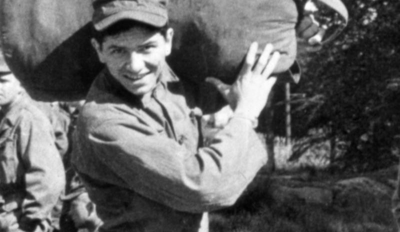 Bill Graham stands in his Army fatigues with a cap on his head and a huge duffel bag over his shoulder.