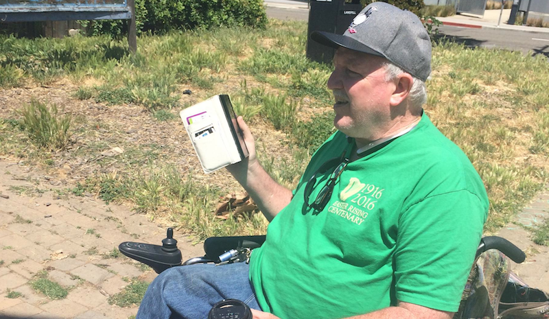 """Street Spirit"" reporter Daniel McMullan talks on his mobile device  at People's Park."