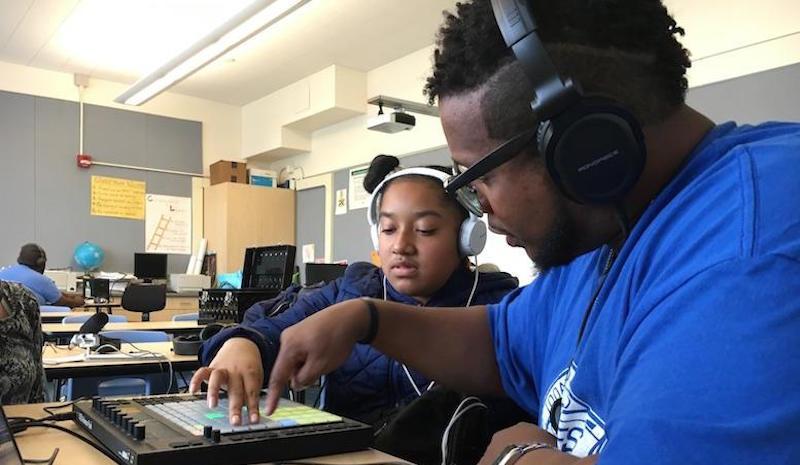 Today's Future Sound instructor Marlon Richardson helps sixth-grader Emily Wayne chose drum beats