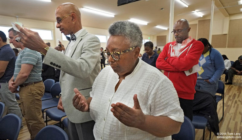 City of Refuge congregants Keith Patterson, at left, and Sylvia Rhue (in white shirt), (both interviewed by Hana Baba), during a prayer portion of the Sunday Sept. 4 service at the City of Refuge United Church of Christ in Oakland.