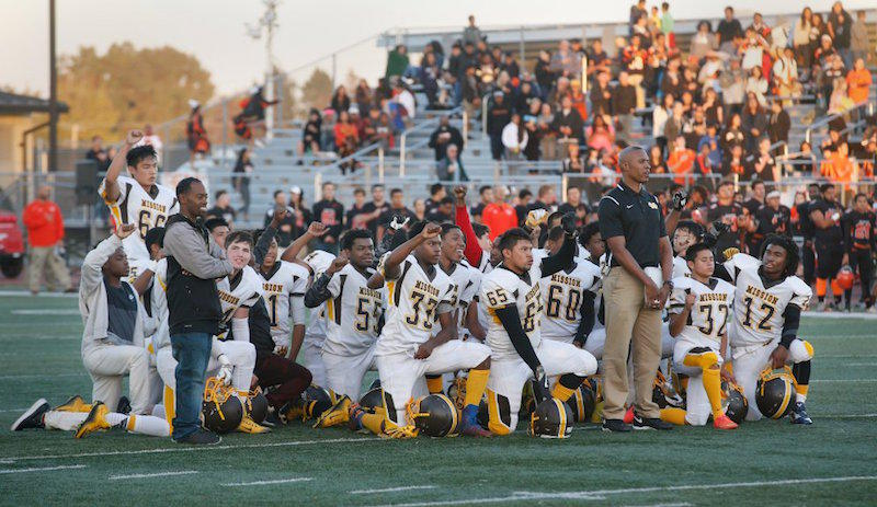 San Francisco's Mission High School football team takes a knee, with the exception of one player, who held up a fist, during the national anthem before their game against San Mateo High School at San Mateo High School.