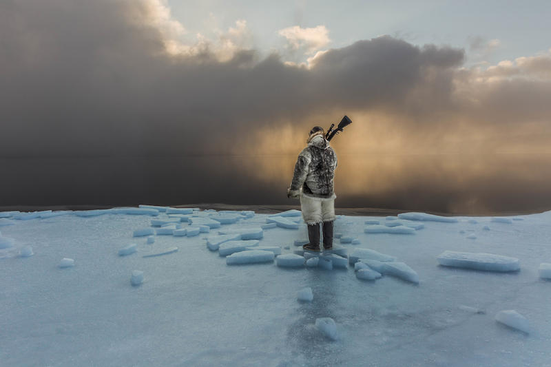"""Last Ice Hunter."" Greenland Inuit Naimanngitsoq Kristiansen keeps watch at the edge of the sea ice, waiting for harp seals or walrus to come near"