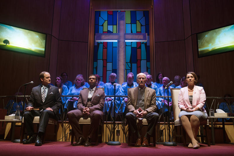 Pastor Paul (Anthony Fusco, left) alongside Associate Pastor Joshua (Lance Gardner), Elder Jay (Warred David Keith) and Paul's wife, Elizabeth (Stephanie Prentice) in 'The Christians'. Behind them the First Unitarian Universalist Society of SF Choir.