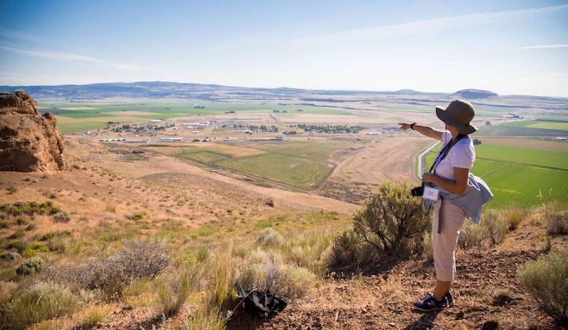 A pilgrimage participant looks down on the former Tule Lake Segregation Center site.