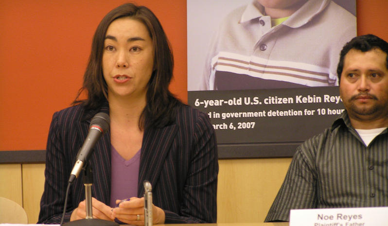 Julia Harumi Mass defending immigrants' rights, specifically the illegal detention of a U.S. citizen, Kevin Reyes.