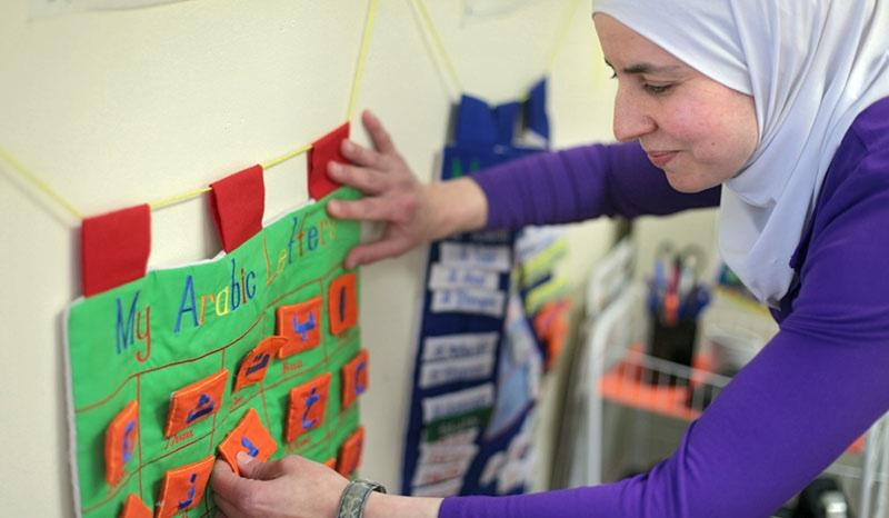 Syrian-born teacher Dania Habboub arranges a chart of Arabic letters after class in Cedar Rapids, Iowa on January 27, 2017.