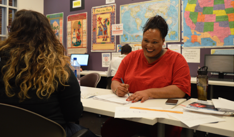 Diamond Electra Star, a patient advocate, sits with her tutor and studies for her GED.