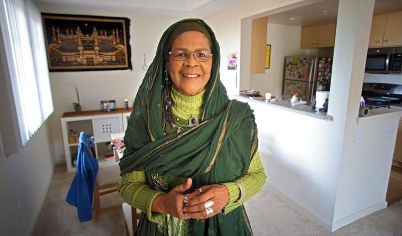 Amina Wadud in her home. Behind her at left is a wall hanging depicting the Kaaba in Mecca.