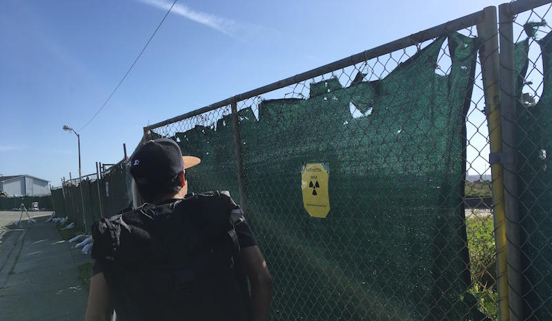 Ben Reyes looks at a radiation sign on a cordond off cleanup site across the street from his Treasure Island home.