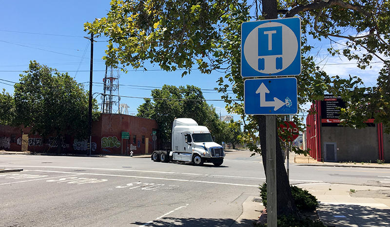 A truck moves along a truck route in West Oakland