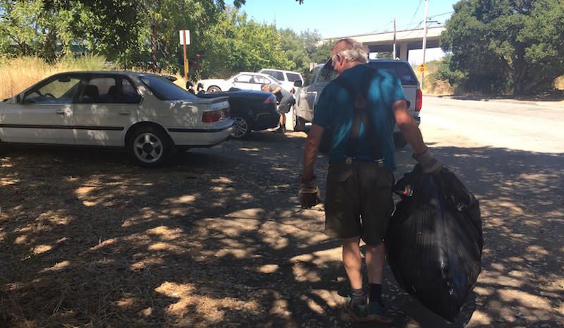 Lomita Park resident Ron Sieg picks up trash days after an oversize vehicle parking ban drove an encampment of RVs out of his neighborhood