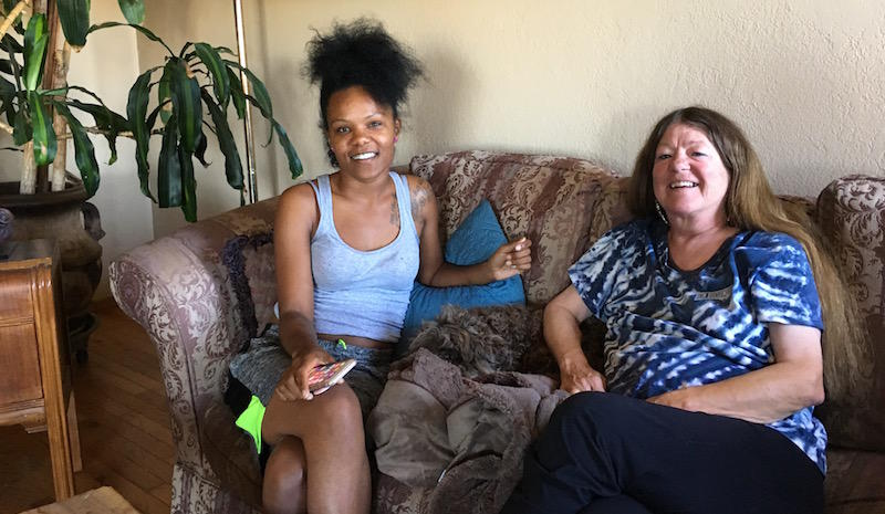 Nikkii Creer (left) and Teryl Burt (right) sit in Burt's living room on two weeks into their stay together as part of the Safe Time program.