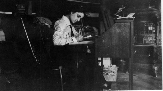 Snapshot of I.W.W. organizer Matilda Robbins, writing at her desk. Photograph was taken in Little Falls, New York.