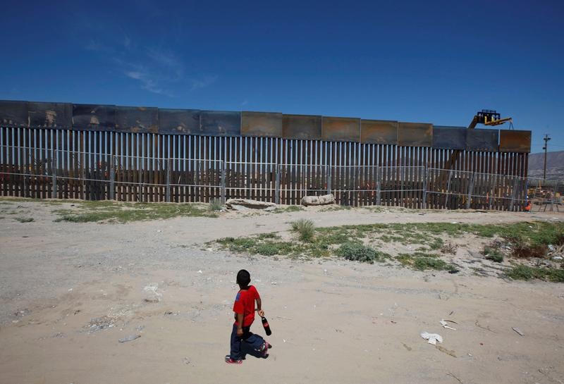 A boy looks at a fence that is part of a section of the U.S.-Mexico border wall at Sunland Park, U.S. opposite the Mexican border city of Ciudad Juarez, Mexico, September 9, 2016. Picture taken from the Mexico side of the U.S.-Mexico border